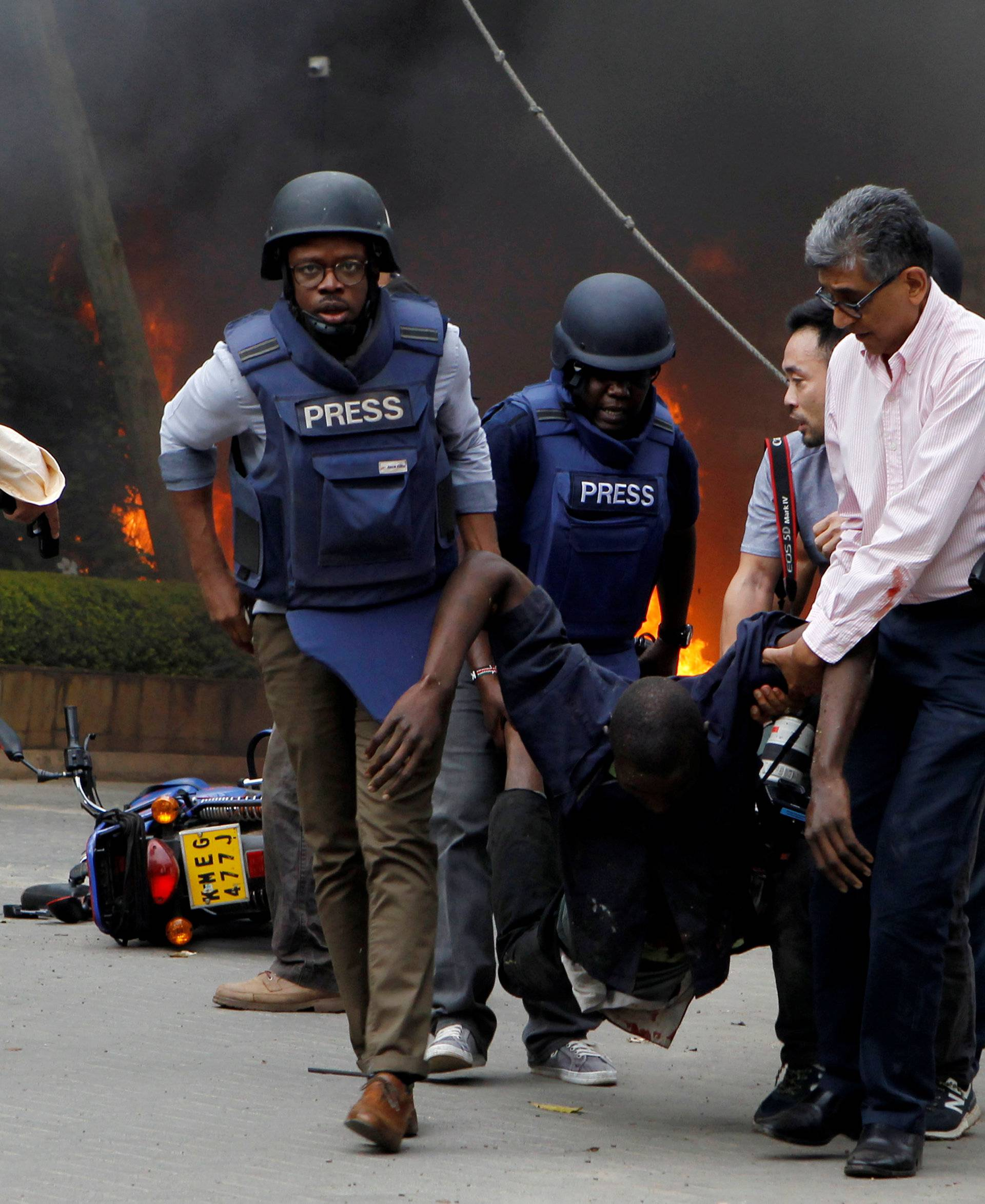 Rescuers and journalists evacuate an injured man from the scene where explosions and gunshots were heard at the Dusit hotel compound, in Nairobi