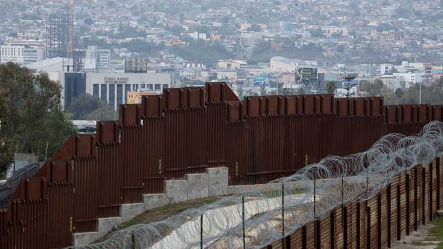 An old border wall fence is shown next to the newly constructed wall along the U.S. Mexico border next to Tijuana, east of San Diego, California