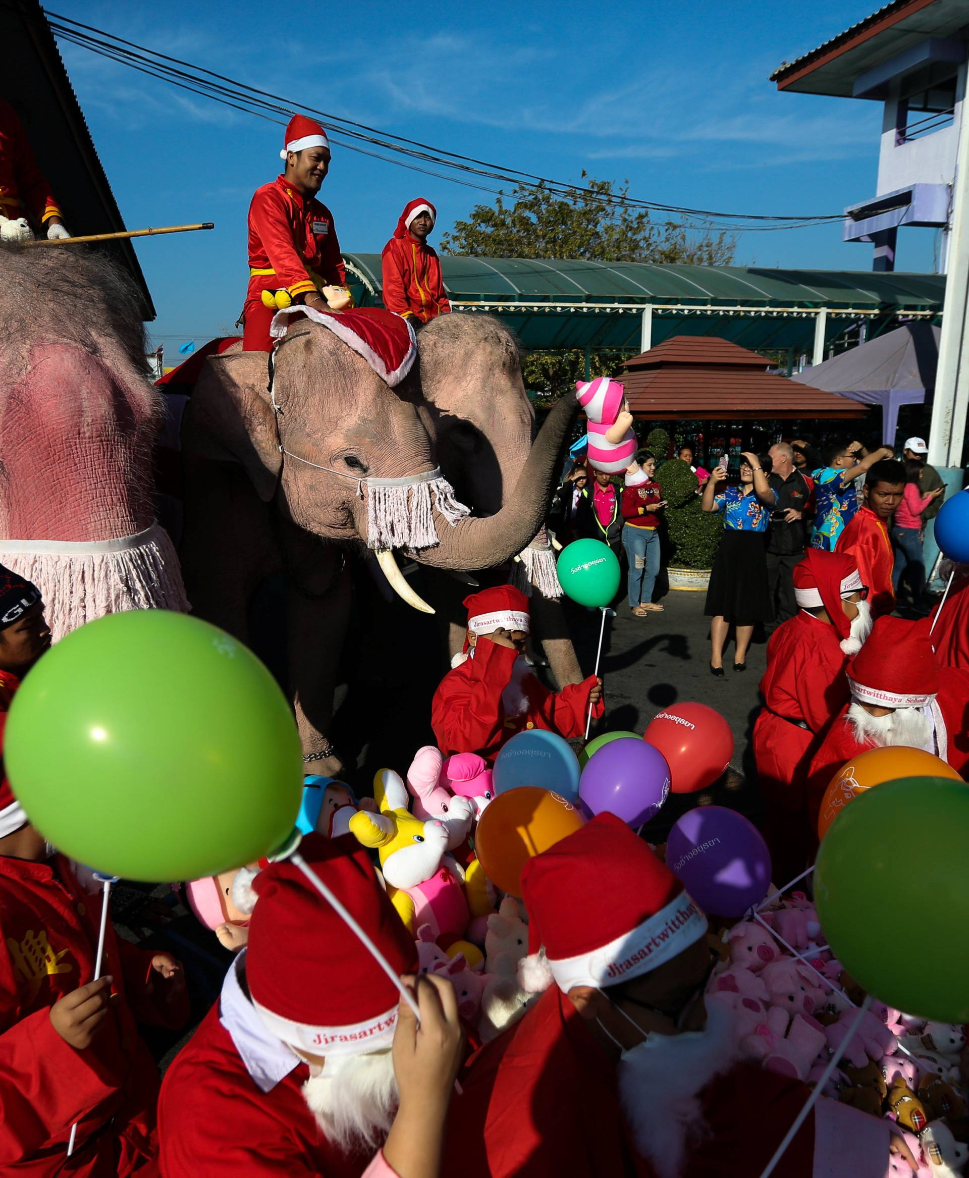 Elephants, teachers and students dressed in Santa Claus costumes parade during Christmas celebrations at Jirasart school in Ayutthaya