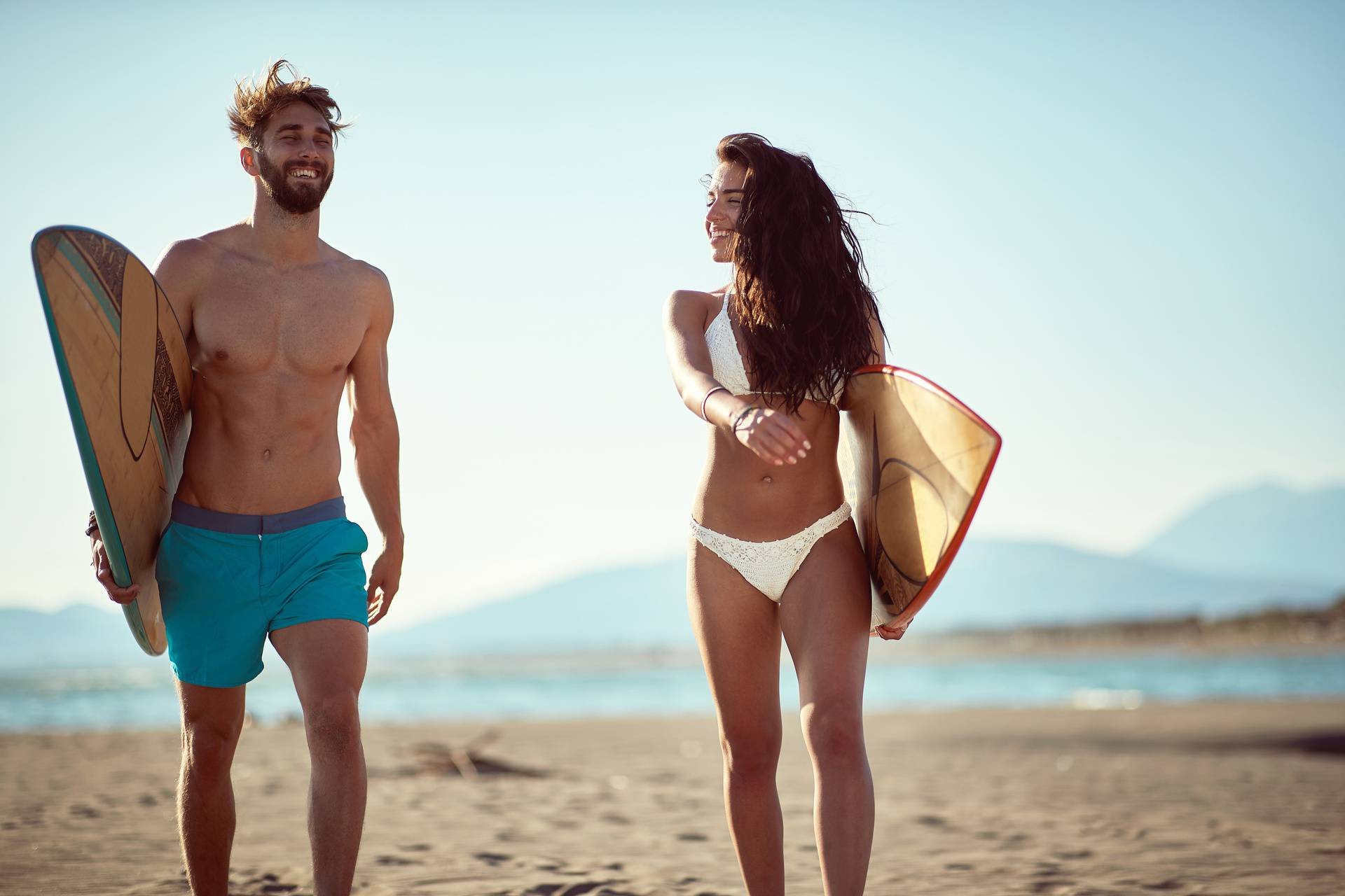 fit, sexy, young  couple walking and talking on beach, holding s