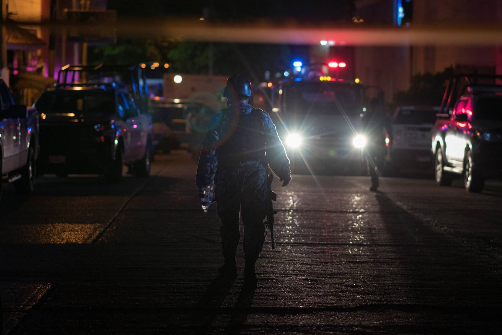 Police officers walk at a crime scene following a deadly attack at a bar by unknown assailants in Coatzacoalcos