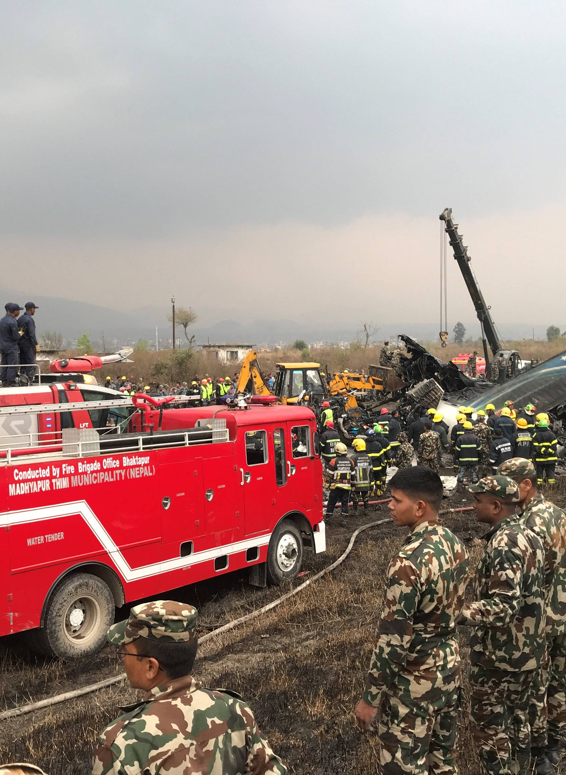 Wreckage of an airplane is pictured as rescue workers operate at Kathmandu airport