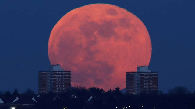 A full moon rises behind blocks of flats in north London,