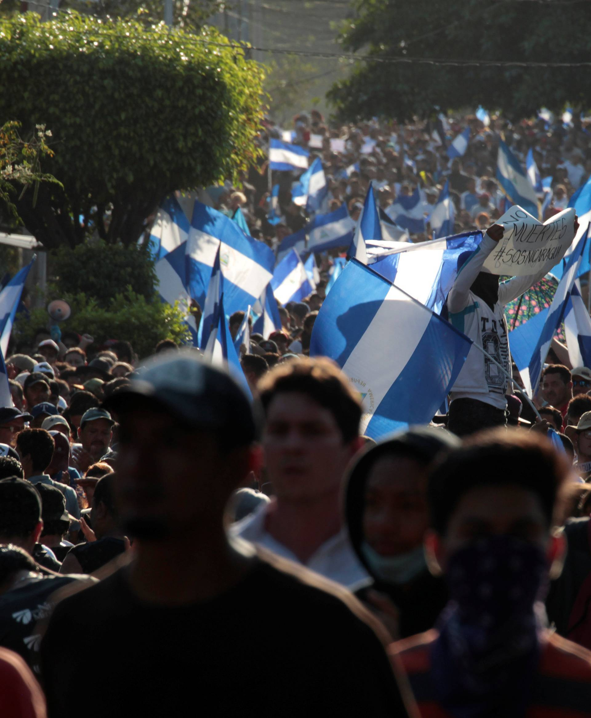 Demonstrators wave flags during a protest against police violence and the government of Nicaraguan President Daniel Ortega in Managua