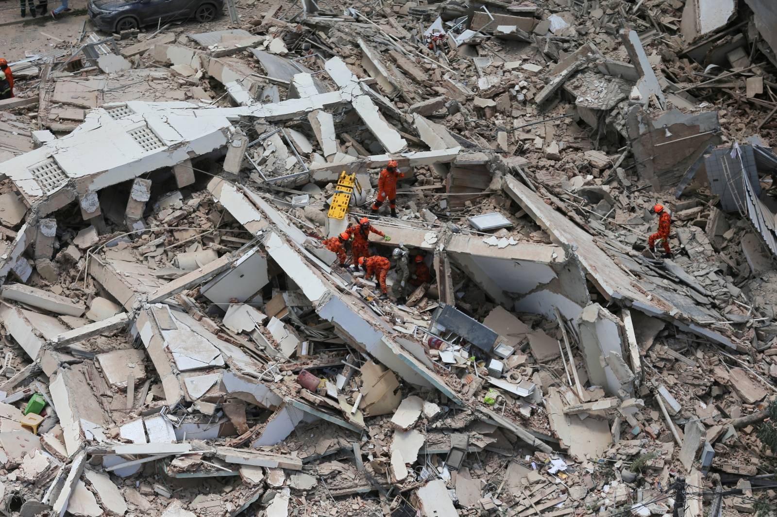 Rescue workers work at the site where a seven-story residential building collapsed in Fortaleza