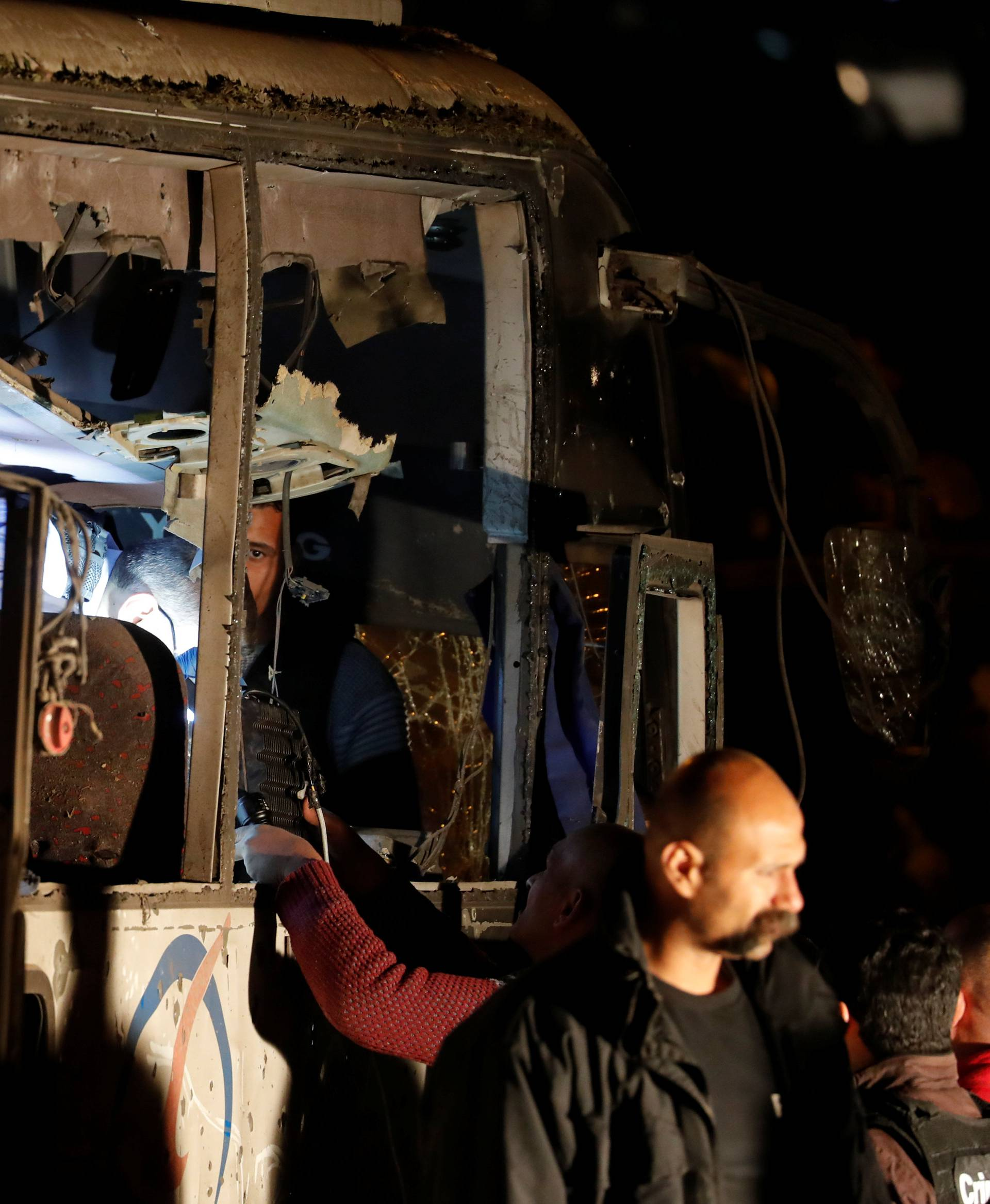 Police officers and officials inspect a scene of a bus blast in Giza