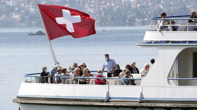 Switzerland's national flag flies above passengers as tourist vessel Limmat sails on Lake Zurich in Zurich