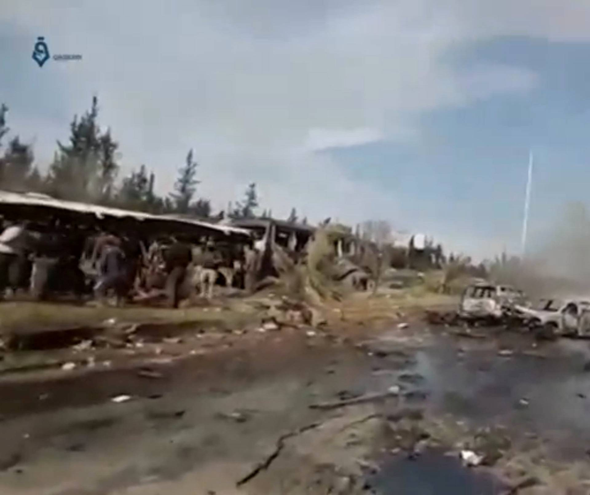A still image taken from a video uploaded on social media on April 15, 2017, shows burnt out buses on road, scattered debris lying nearby and injured people being tended to away from buses said to be in Aleppo