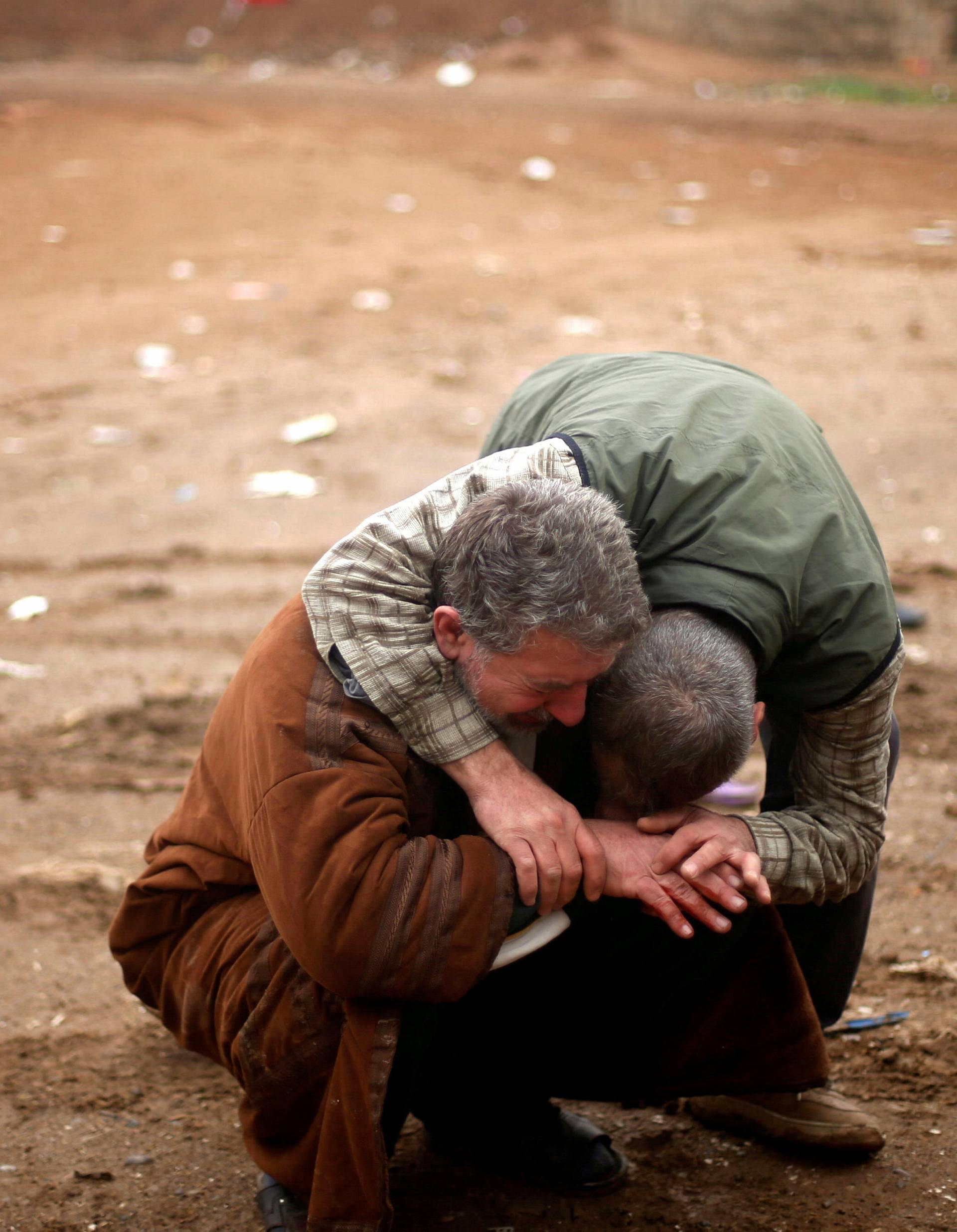 An Iraqi father mourns the death of his son, who was killed during clashes in the Islamic State stronghold of Mosul, in al-Samah neighborhood, Iraq