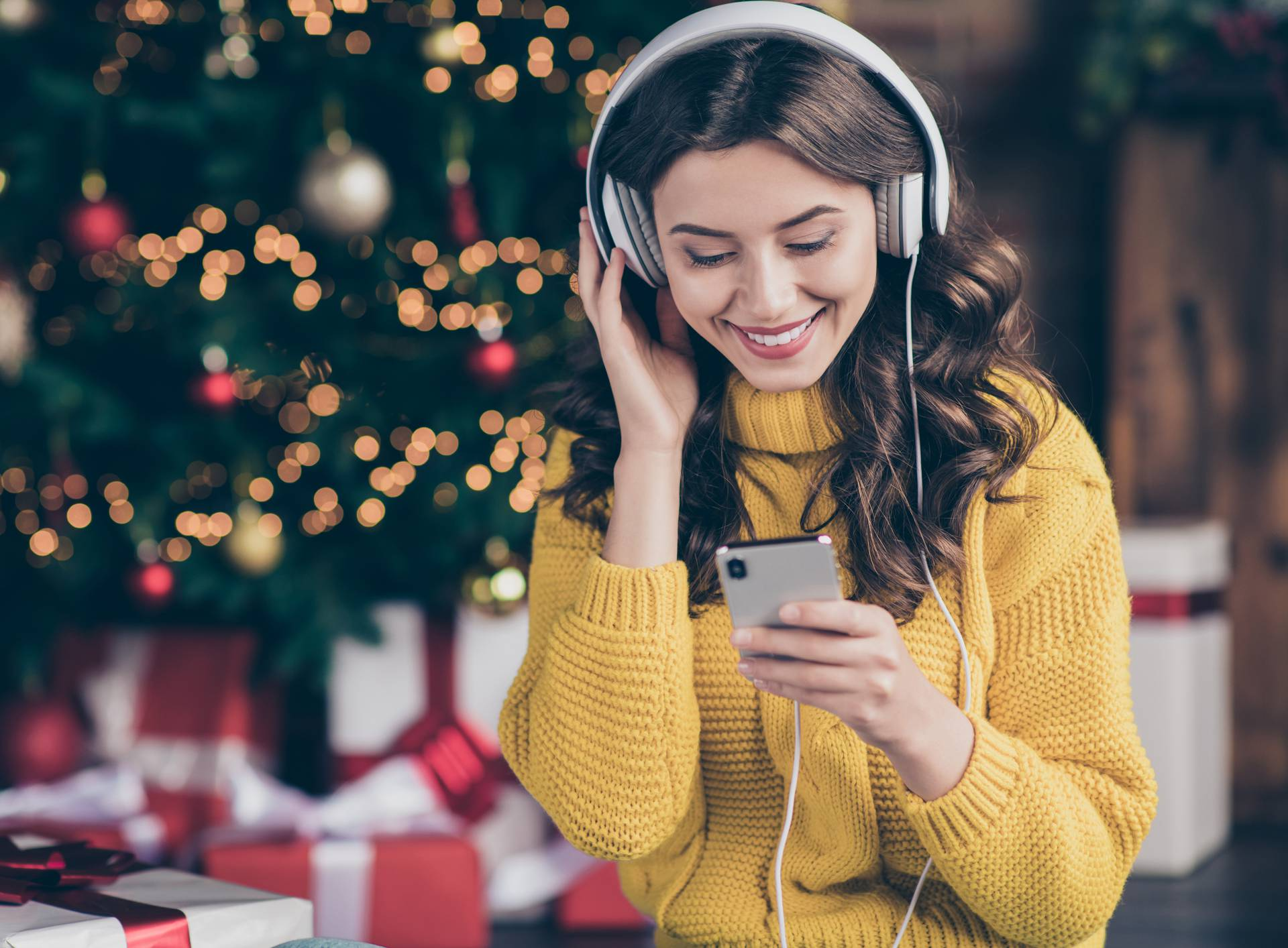 Photo of charming beautiful wavy curly haired girl listening to music wearing yellow pullover staring at telephone screen