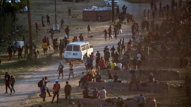 Migrants seeking asylum in the U.S. wait to be processed under the International Bridge in Del Rio