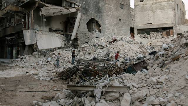 Boys make their way through the rubble of damaged buildings in the rebel held area of al-Kalaseh neighbourhood of Aleppo