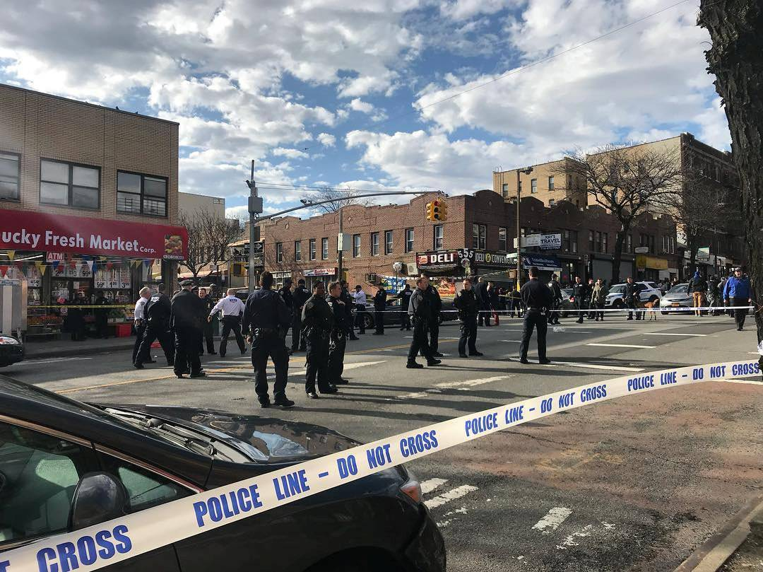 Police officers stand behind a cordon tape at the scene of a shooting in Brooklyn, New York