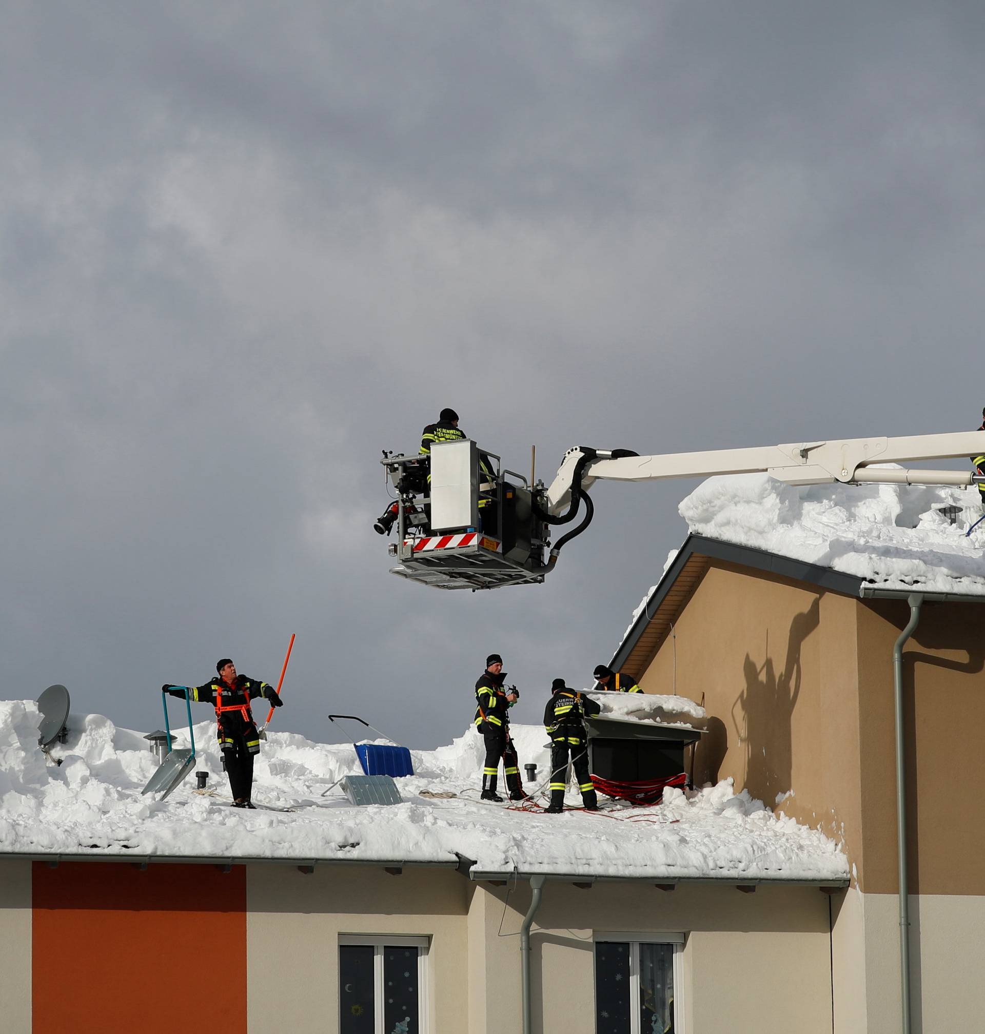 Members of the fire brigade shovel snow on a rooftop after heavy snowfall in Rosenau