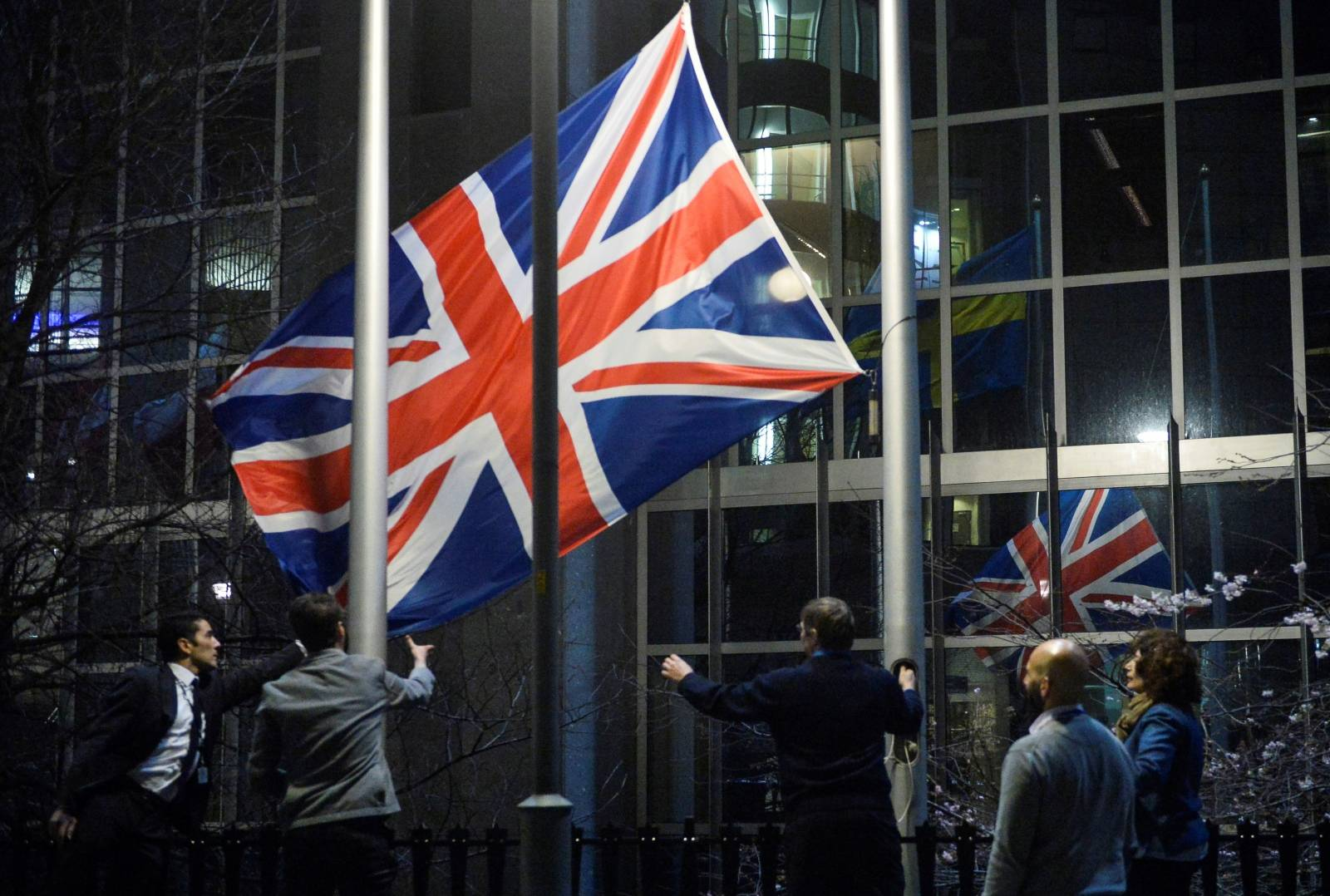 Workers remove the British flag outside the European Parliament building, as Britain leaves the European Union, in Brussels