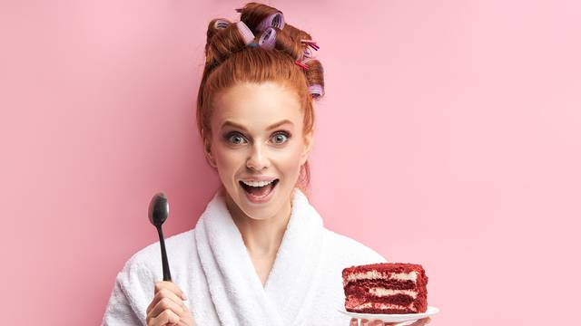 Happy young woman going to eat tasty cake on pink background
