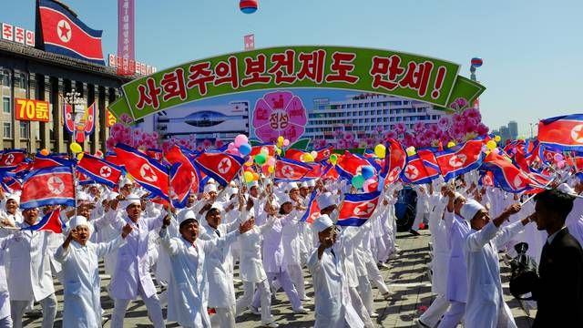 North Koreans march alongside a float celebrating the country's socialist health system during a parade in Pyongyang