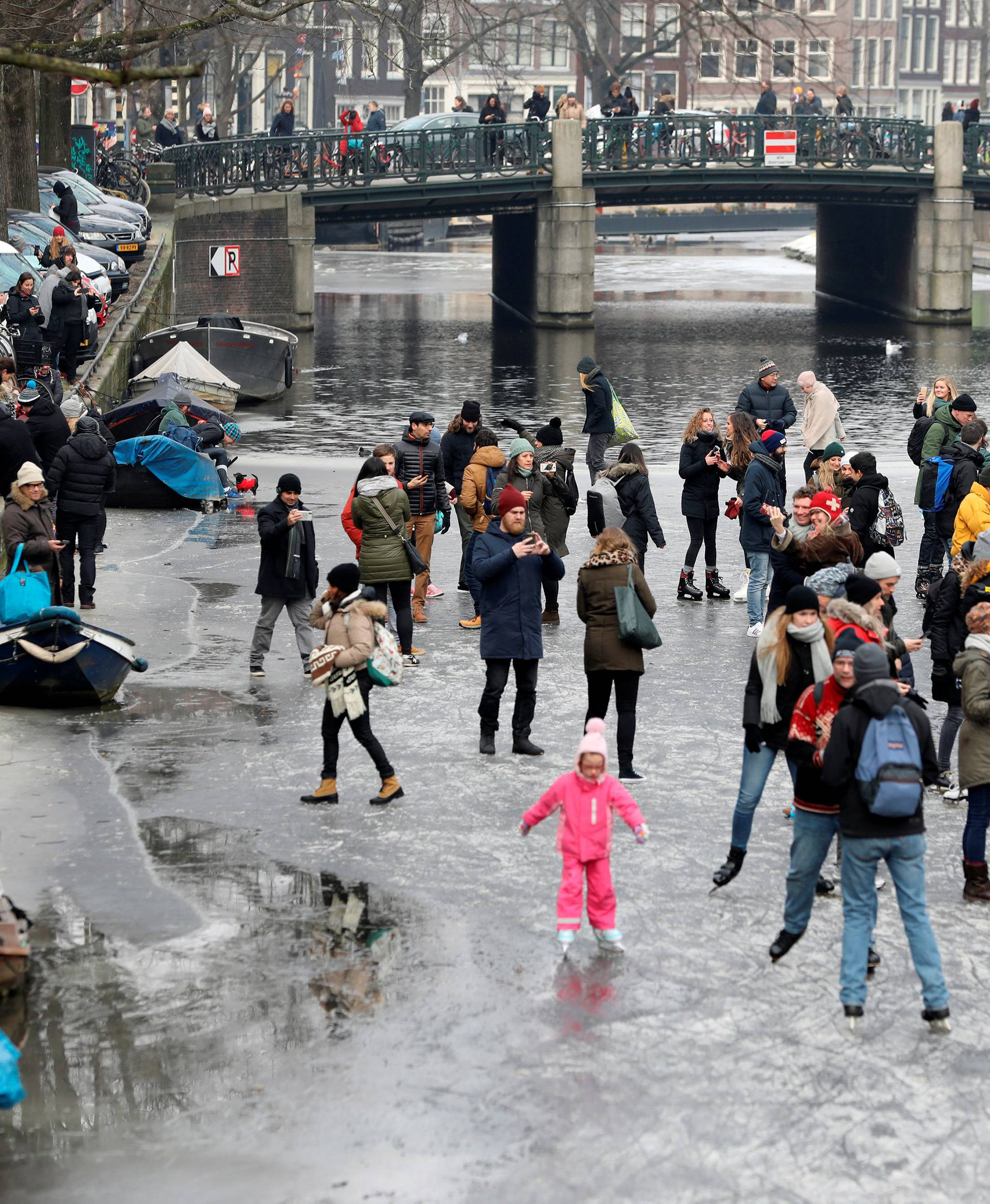 Ice skaters skate and walk on the frozen Prinsengracht canal during icy weather in Amsterdam