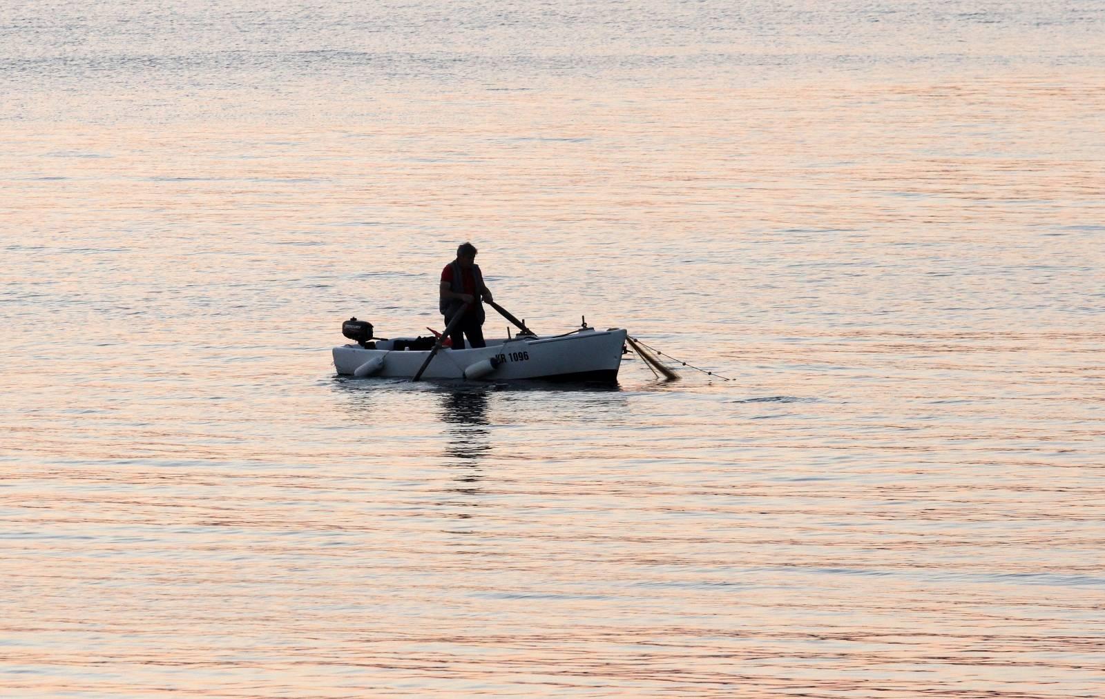 Ribar na moru pred Kostrenom spušta mrežu u more