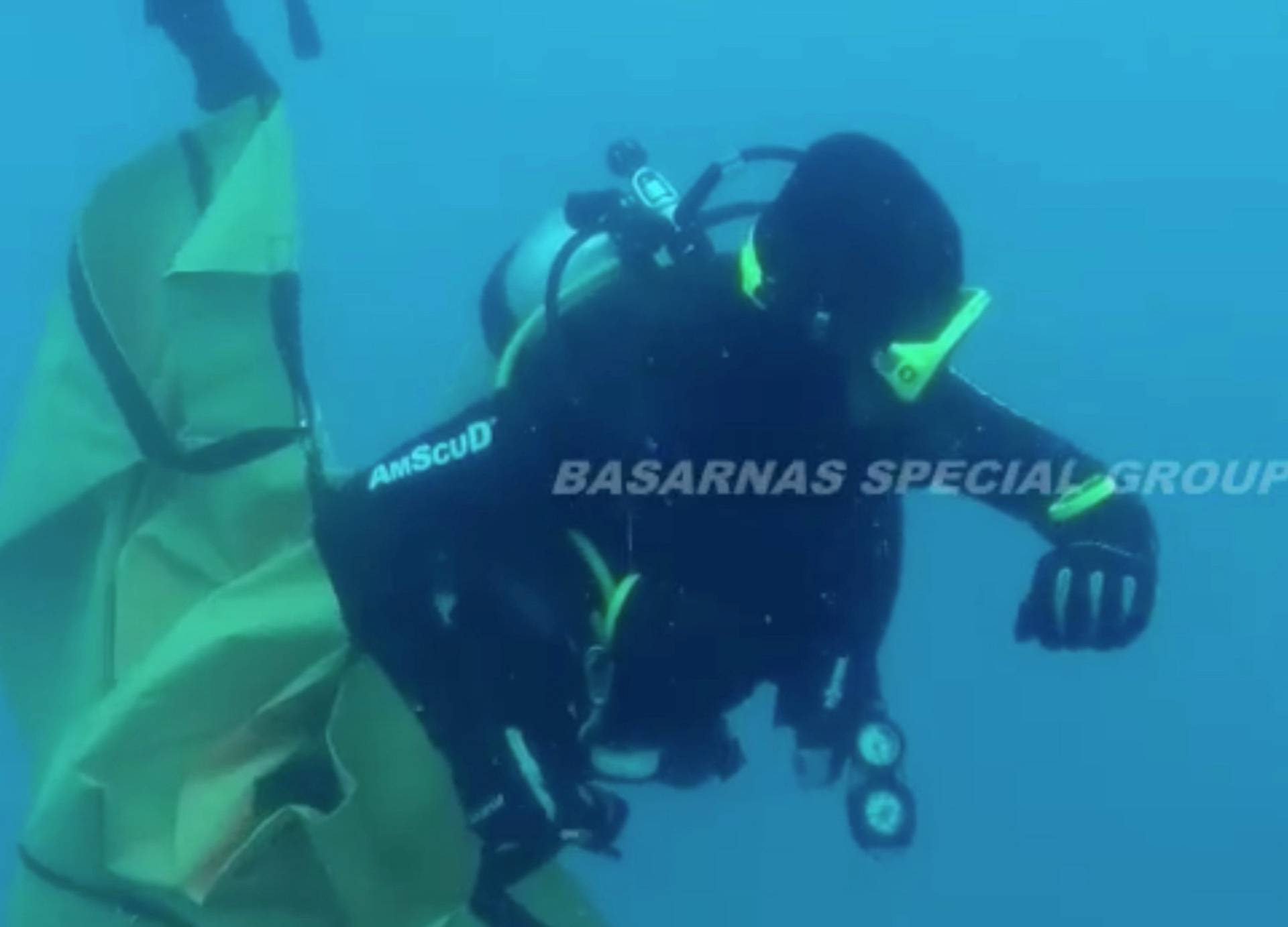 Divers collect debris in a bag in the search area for Lion Air's flight JT610 airplane, in Indonesia