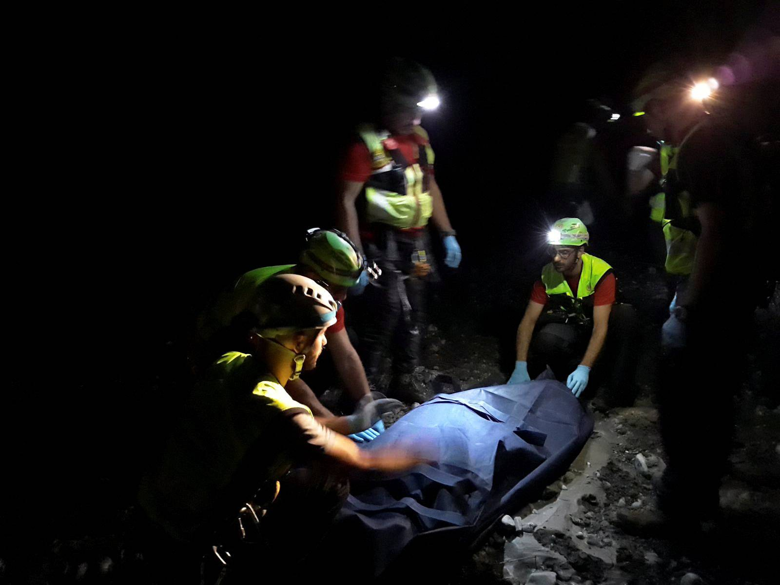 Alpine rescue workers carry a body after several people were killed in a mountain gorge flooding, in the municipality of Civita