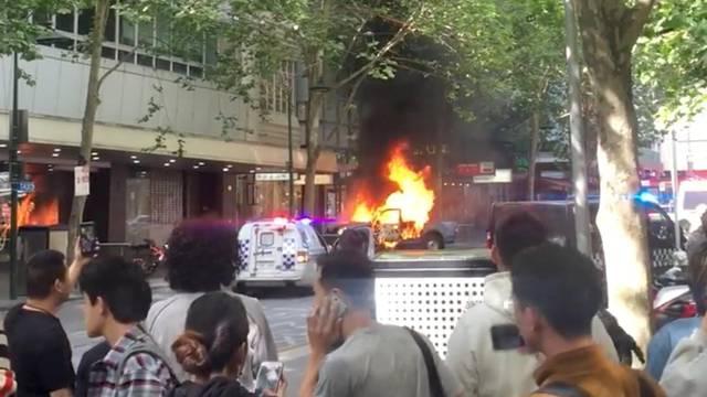 A burning car is seen on Bourke Street, in Melbourne