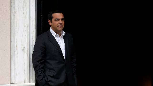 Greek Prime Minister Alexis Tsipras waits for former French President Francois Hollande at his office in the Maximos Mansion in Athens