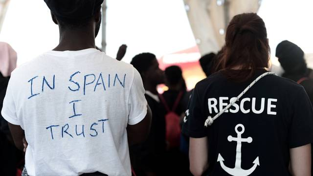 "A migrant wearing a t-shirt reading ""In Spain I Trust"" waits to disembark from the Aquarius rescue ship at port in Valencia"