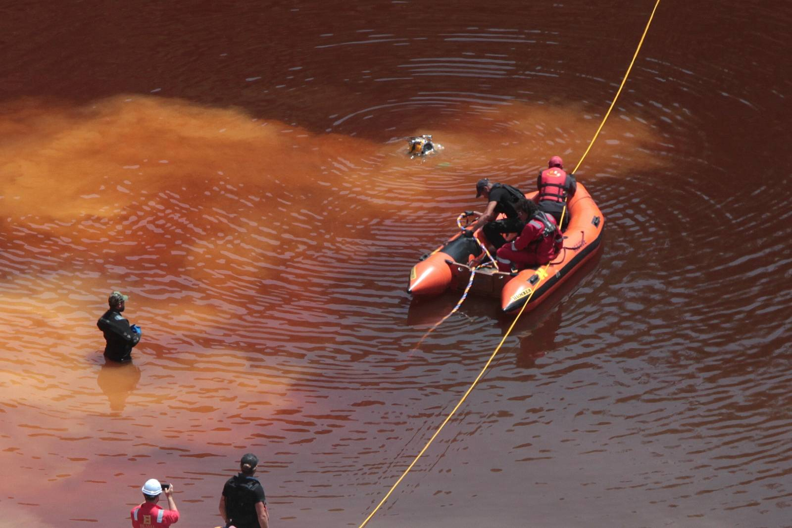Police forensics officers, rescuers and divers retrieve a suitcase near the village of Mitsero