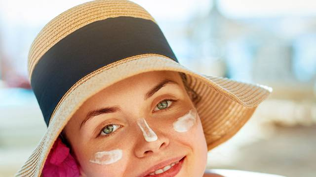Skincare. Beauty Concept. Young pretty woman holding  sun cream and applying on her face. Female in hat smear  sunscreen lotion on skin and touch own face. Skin Protection and dermatology.