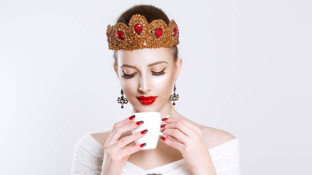 Looking down beautiful woman with white mug of hot beverage in hand