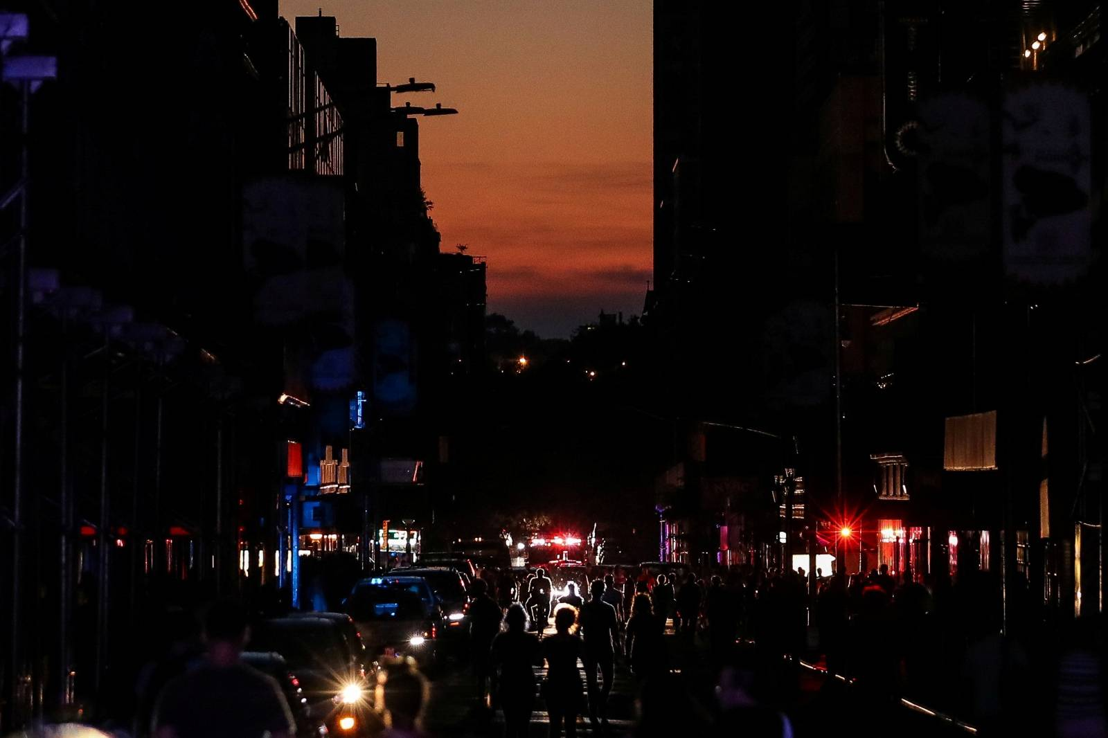 People walk along a dark street near Times Square area, as a blackout affects buildings and traffic during widespread power outages in the Manhattan borough of New York