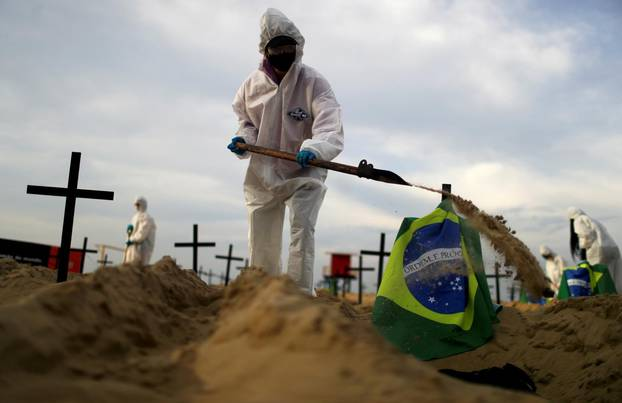 Activists of the NGO Rio de Paz in protective gear dig graves on Copacabana beach to symbolise the dead from the coronavirus disease (COVID-19) during a demonstration in Rio de Janeiro
