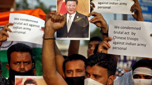 Demonstrators hold placards and a defaced poster of Chinese President Xi Jinping as they shout slogans during a protest against China, in Ahmedabad