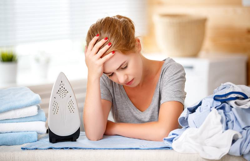 tired woman housewife ironing clothes iron in laundry