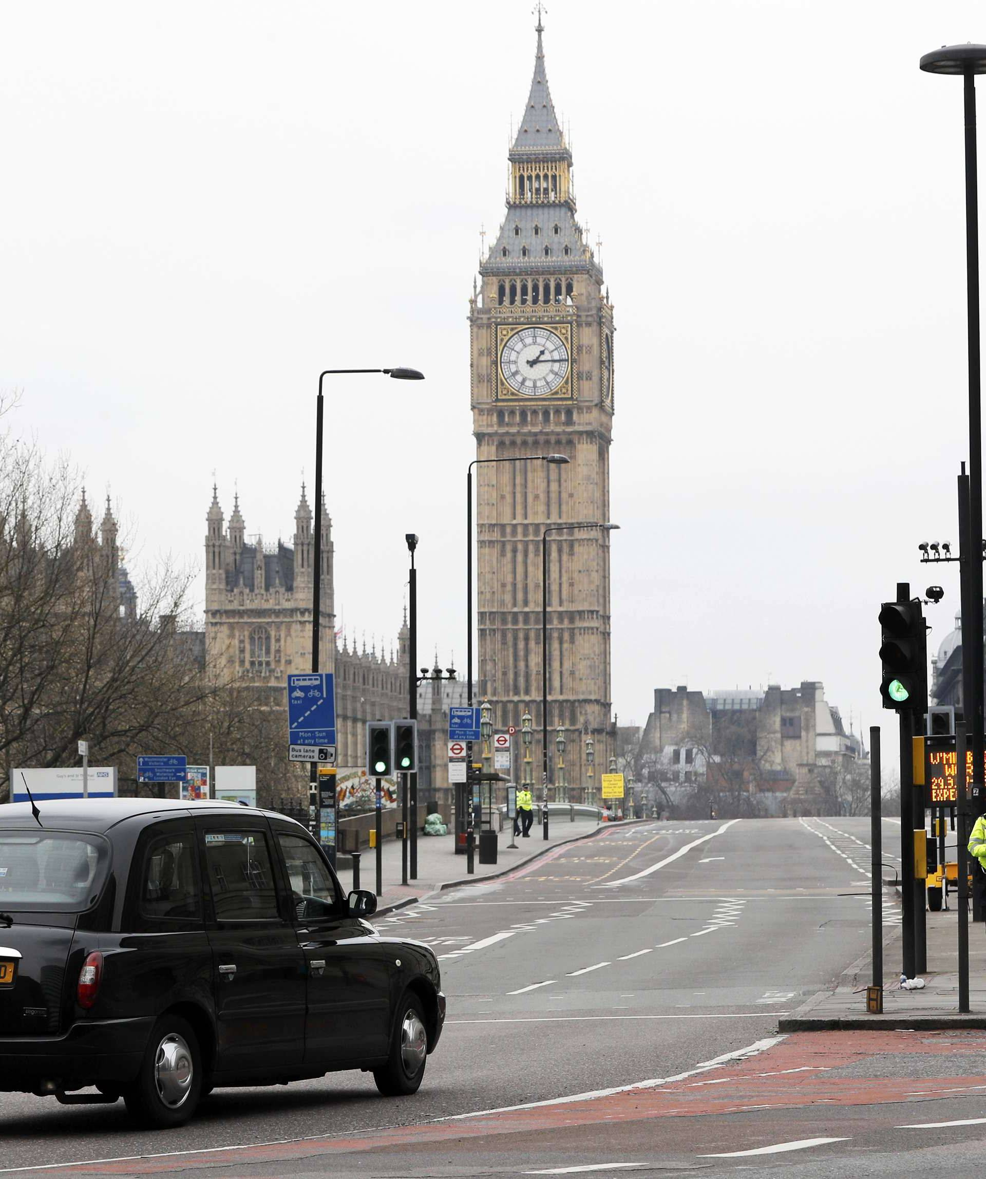 A police motorbike and a London Taxi are the first vehicles to cross Westminster Bridge as it is re-opened after an attack in London