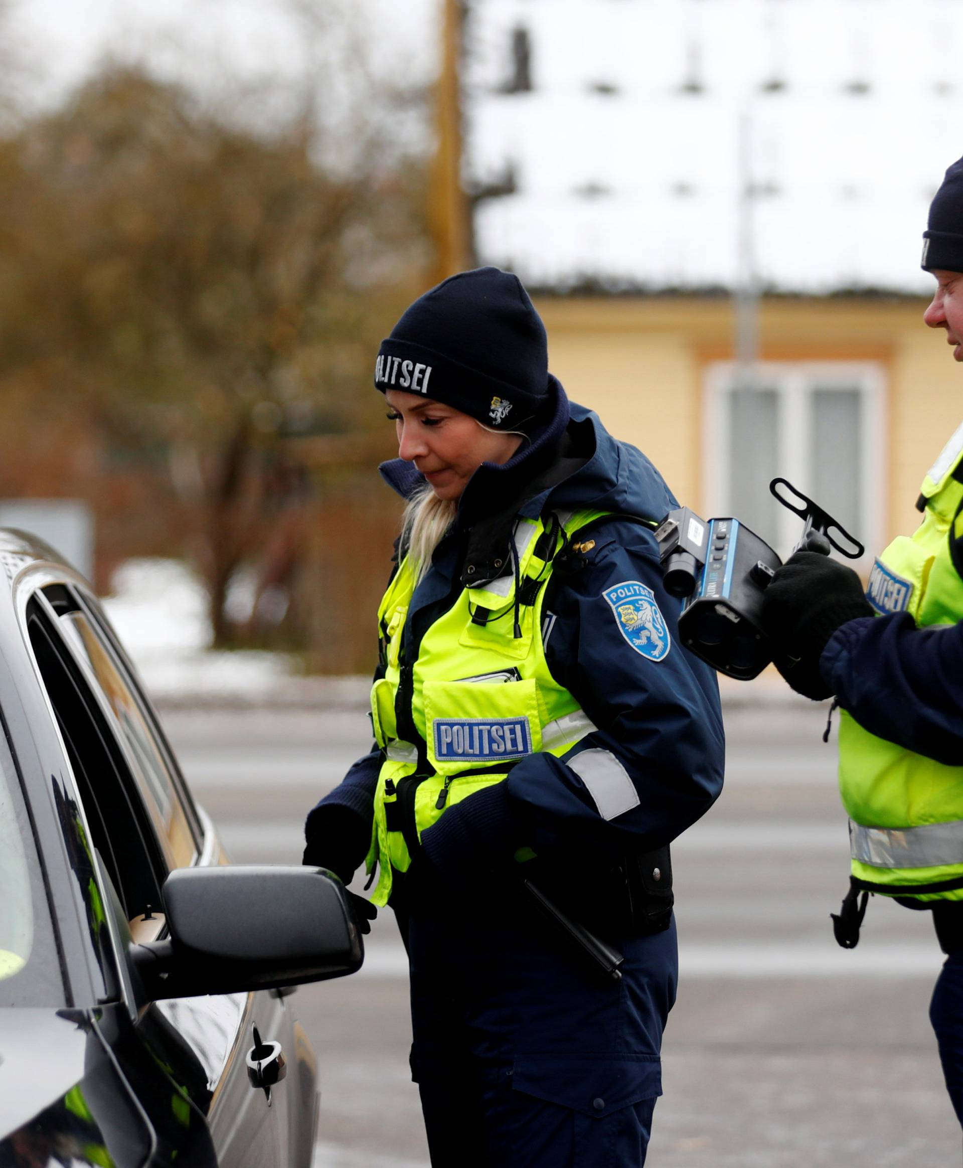 Estonian police officers Hele Truus and Aimar Luik talk to a speeding driver in Parnu