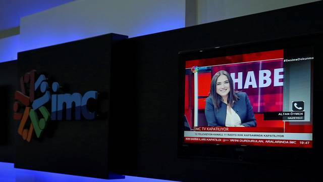 News anchor Banu Guven is seen on a screen during a news broadcast at a studio of IMC TV, a news broadcaster slated for closure, in Istanbul