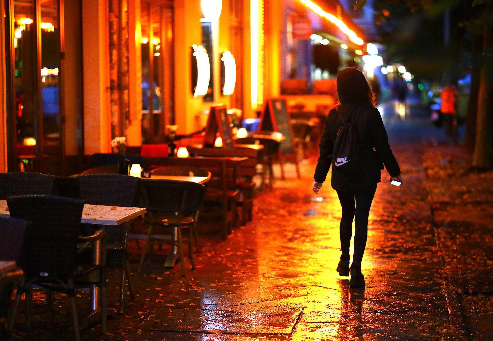 A woman passes empty tables before the late-night curfew due to restrictions against the spread of the coronavirus disease (COVID-19)in Berlin