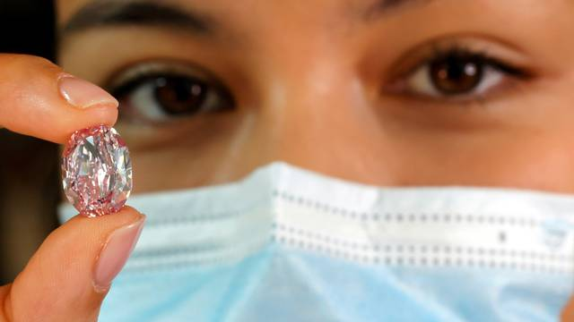 """FILE PHOTO: A model poses with """"The Spirit of the Rose"""" purple-pink diamond in Geneva"""