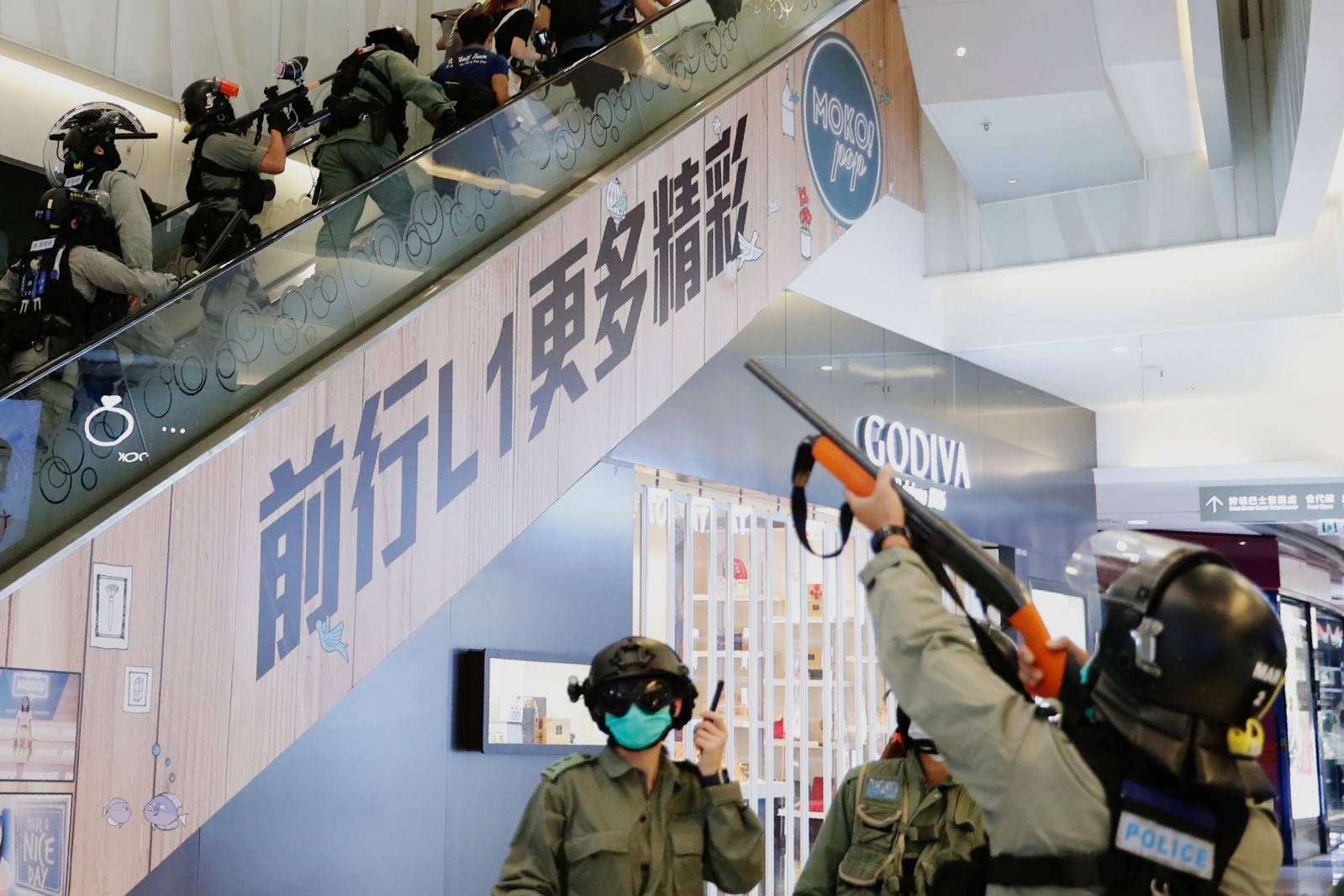 Riot police raise their pepper spray projectile inside a shopping mall as they disperse anti-government protesters during a rally, in Hong Kong