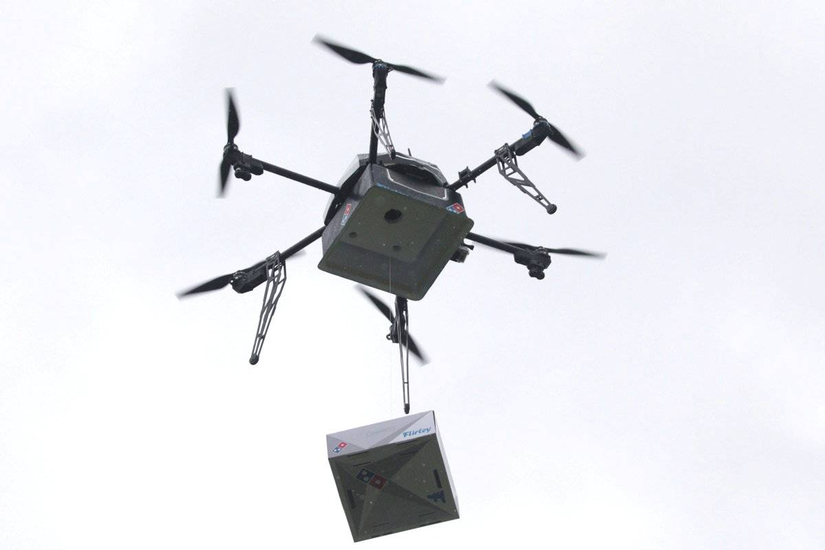 A delivery drone performs a test flight with a Domino's pizza box in Auckland, New Zealand