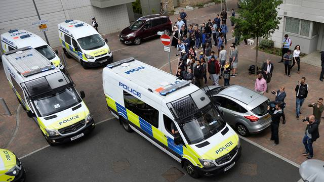 Police vans leave carrying a number of women who were detained after a block of flats was raided in Barking, east London