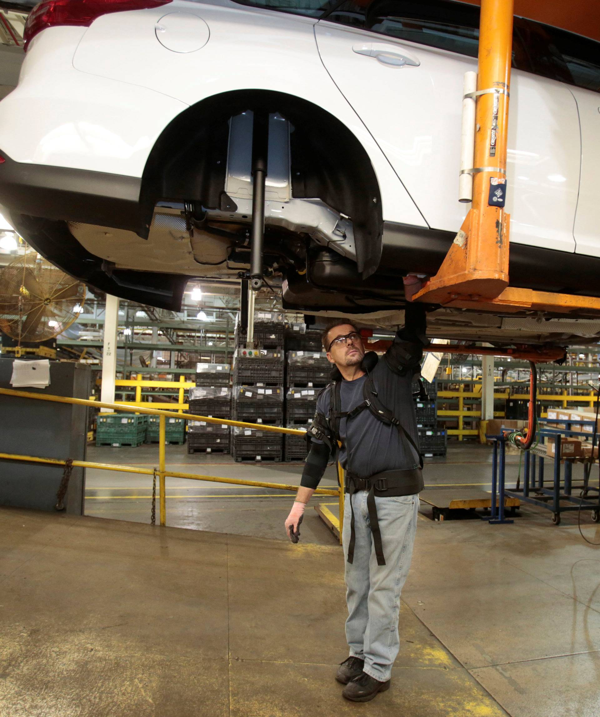 Ford Motor Co assembly worker Paul Collins wears an EksoVest as he works on the assembly line producing the Ford Focus and C-max at Wayne Assembly plant in Wayne