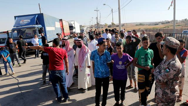 People gather while trucks loaded with humanitarian supplies to be delivered for displaced Syrians, wait at the Jordanian city of Mafraq