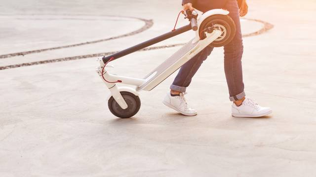 Person carrying folded electric scooter along road