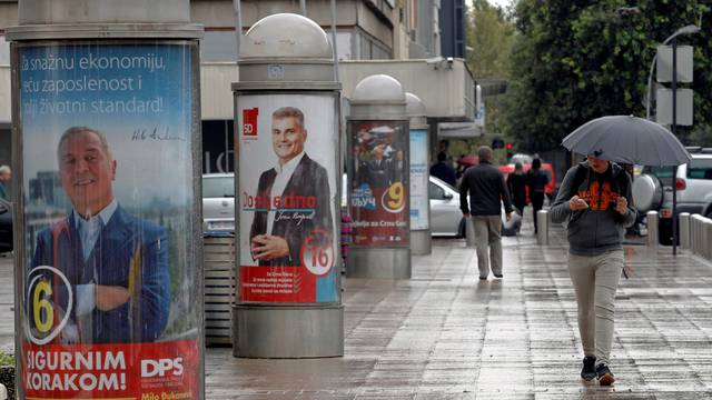 A man walks past election posters ahead of the parliamentary elections in Podgorica