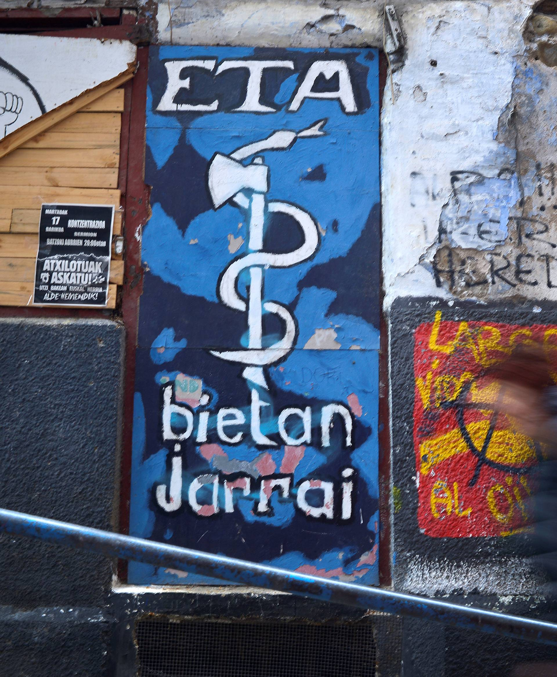A woman walks past a mural depicting the serpent and axe emblem of armed Basque separatists ETA in Bermeo