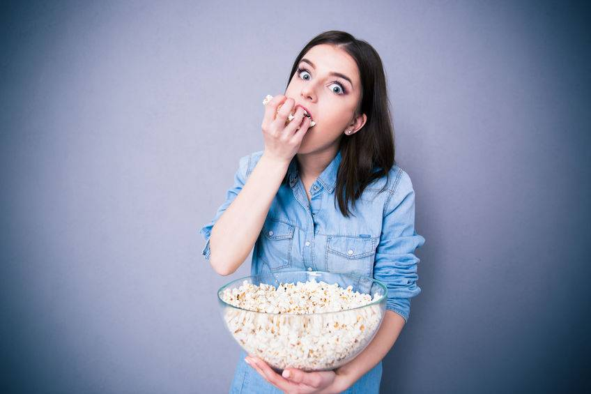 Young cute woman eating popcorn