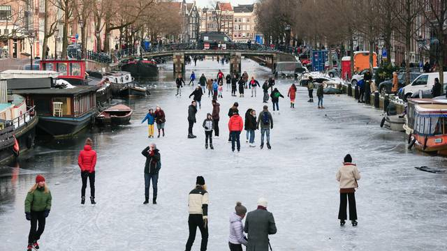 People ice skate during a cold snap across the country at the canals in Amsterdam